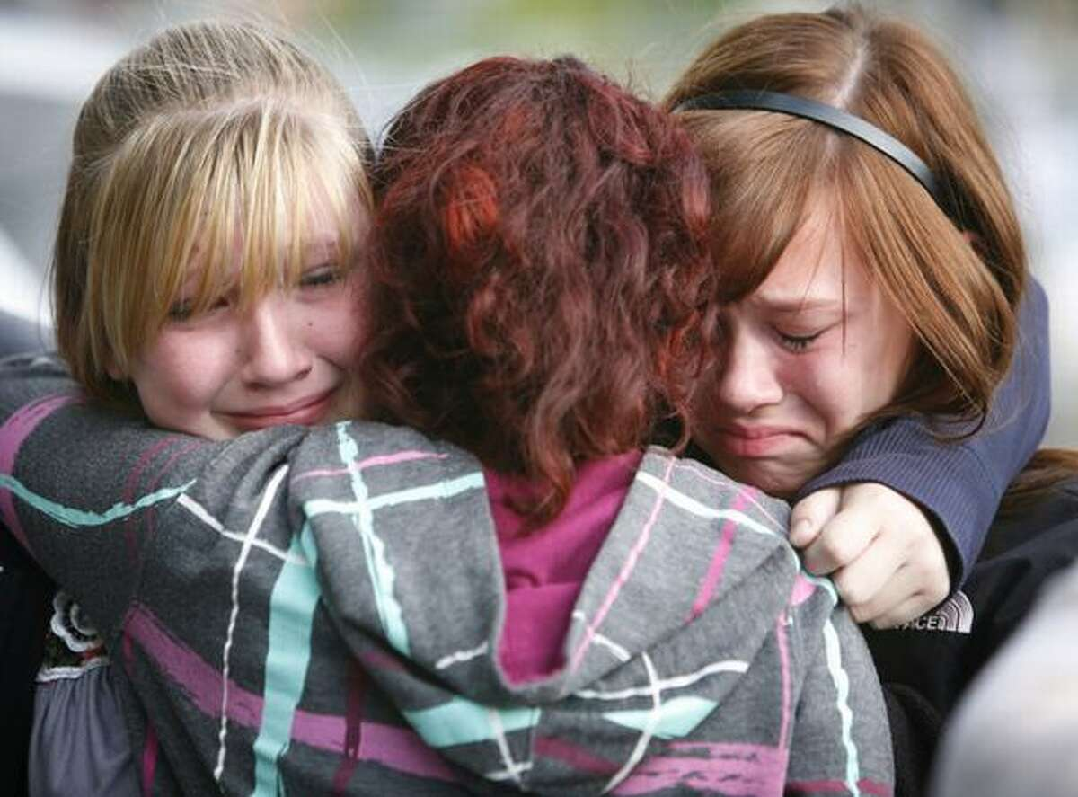 From left, Tasha Leton, 12, Angelique Davenport, 13, and Alexis Niemi, 13, embrace during a vigil for their classmate and good friend Alajawan Brown, 12, in the parking lot of a 7-Eleven store on Martin Luther King Way South and South 129th Street in Skyway. Alajawan Brown died in the parking lot of the convenience store on April 29 when he was shot after getting off the bus.