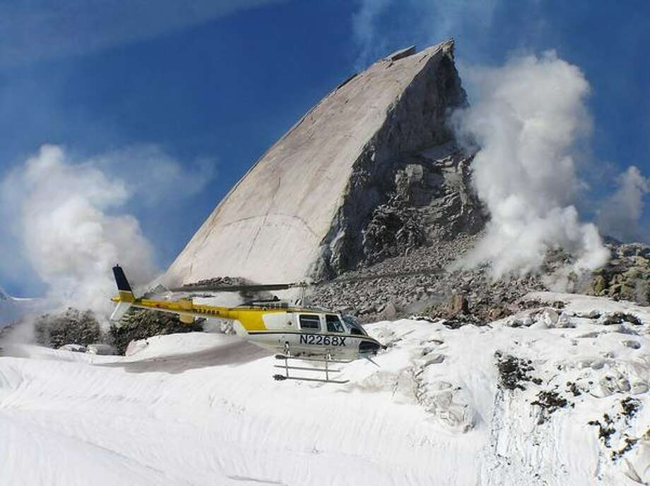 """In this photo provided by the USGS, a helicopter flies past a new """"slab"""" rock growth in the crater of Mount St. Helens, Friday, April 28, 2006. (AP Photo/USGS Cascades Volcano Observatory, Dan Dzurisin) Photo: P-I File"""