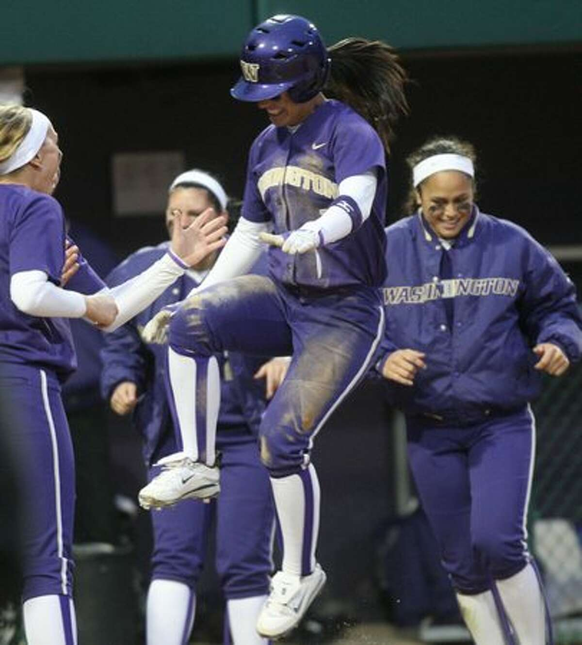 University of Washington player Jenn Salling leaps onto home plate after being driven home by a Shawna Wright home run against the University of Oklahoma during Game 2 of a double-header in the NCAA Super Regionals on Friday, May 28, 2010 at Husky Stadium.