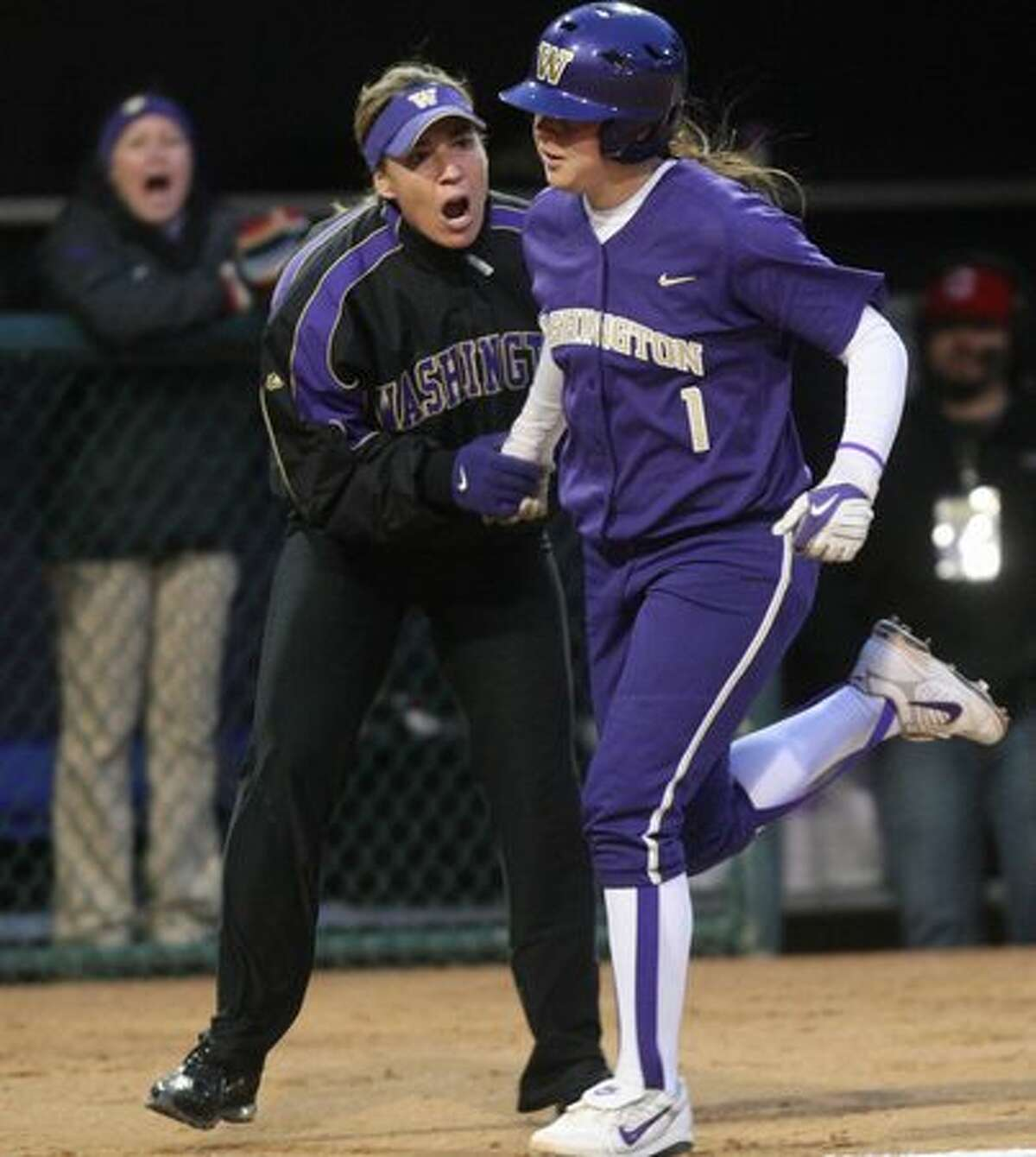 University of Washington player Shawna Wright rounds third base and celebrates with head coach Heather Tarr after Wright hit a home run against the University of Oklahoma during the third in a series of games in the NCAA Super Regionals on Friday May 28, 2010 at Husky Stadium.