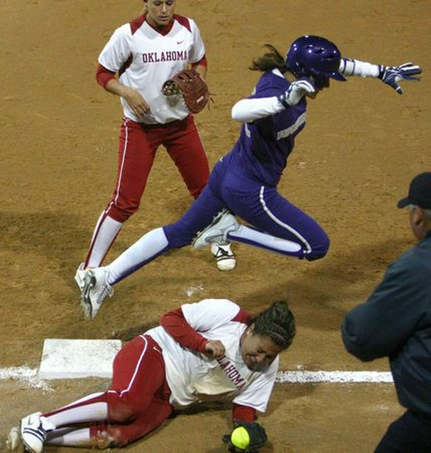 University of Washington player Alyson McWherter leaps over University of Oklahoma player Amber Flores during the third in a series of games in the NCAA Super Regionals on Friday May 28, 2010 at Husky Stadium. Photo: Joshua Trujillo, Seattlepi.com