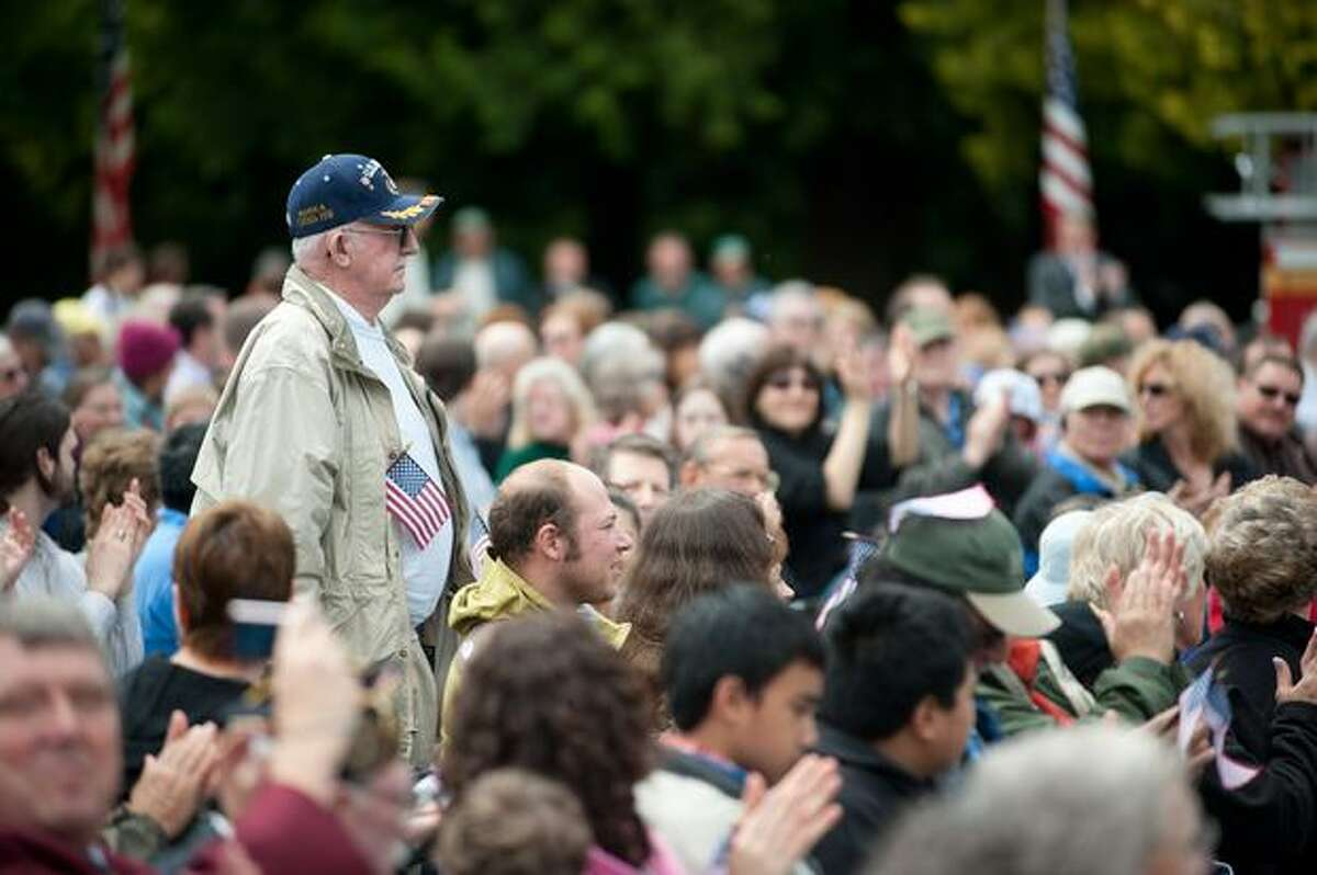 Veterans rise to applause as their song is played during a Memorial Day service in Seattle.