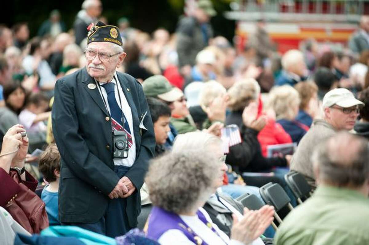 Veterans rise to applause as their song is played during a Memorial Day service.