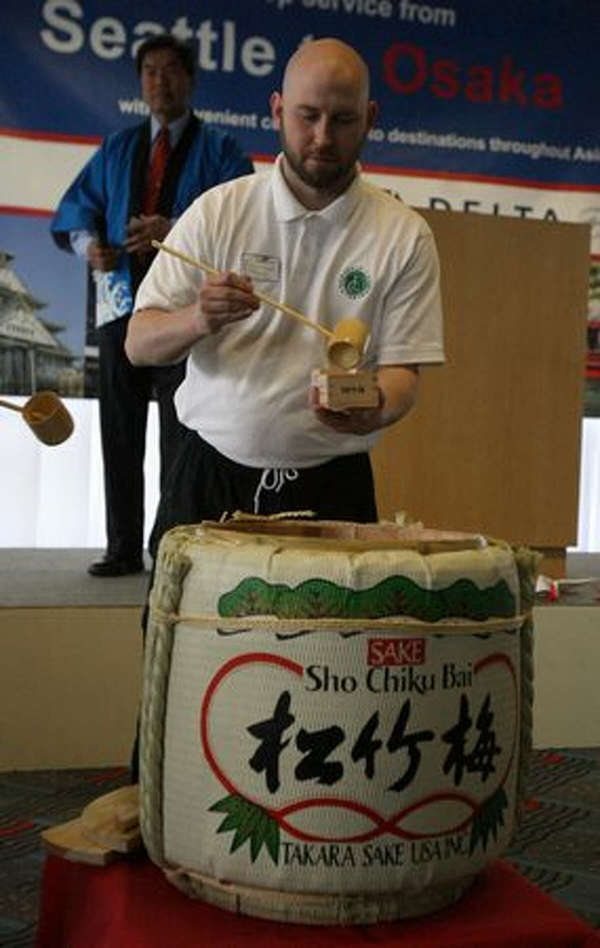 A server pours sake during a ceremony at SeaTac Airport marking the start of Delta Air Lines' nonstop flights between Seattle and Osaka, Japan.