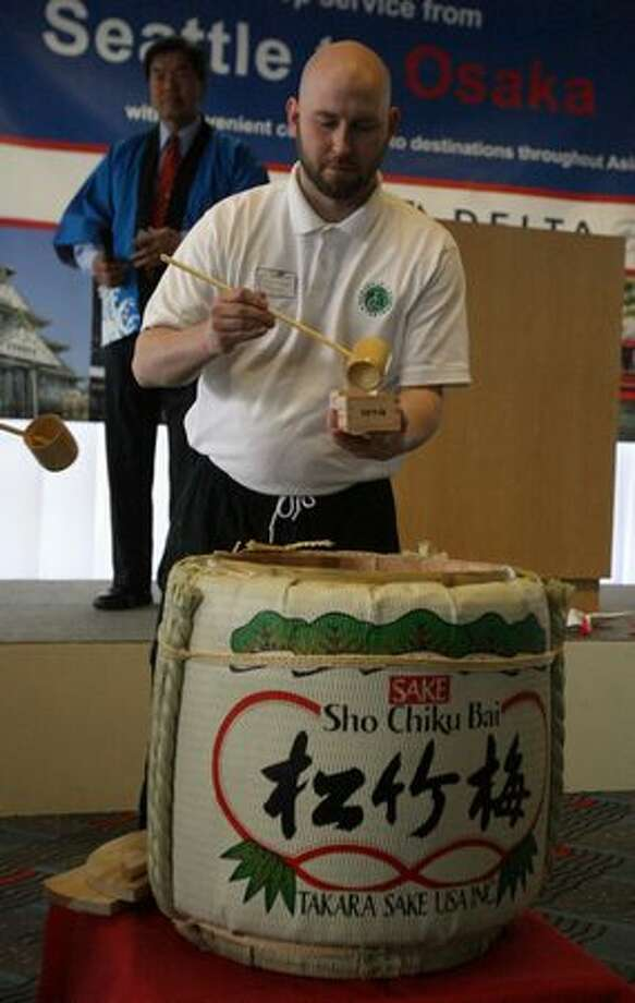 A server pours sake during a ceremony at SeaTac Airport marking the start of Delta Air Lines' nonstop flights between Seattle and Osaka, Japan. Photo: Aubrey Cohen, Seattlepi.com
