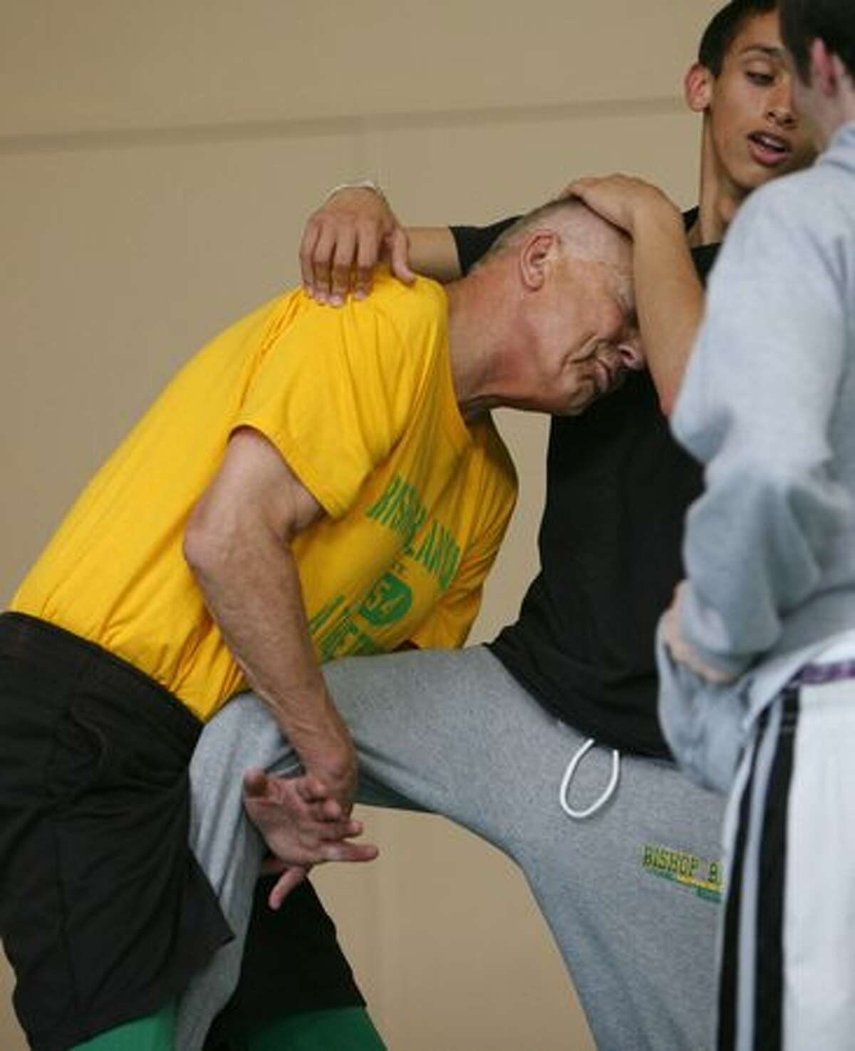 Bishop Blanchet coach Bill Herber, 74, takes a student to the mat during a wrestling clinic at the school in north Seattle. Herber has been a coach, teacher and friend to generations of students that have attended Blanchett. He retired this year after 50 years teaching at the Catholic school.