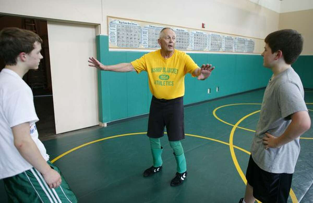 Long-time Bishop Blanchet coach and teacher Bill Herber works with students during a wrestling camp.