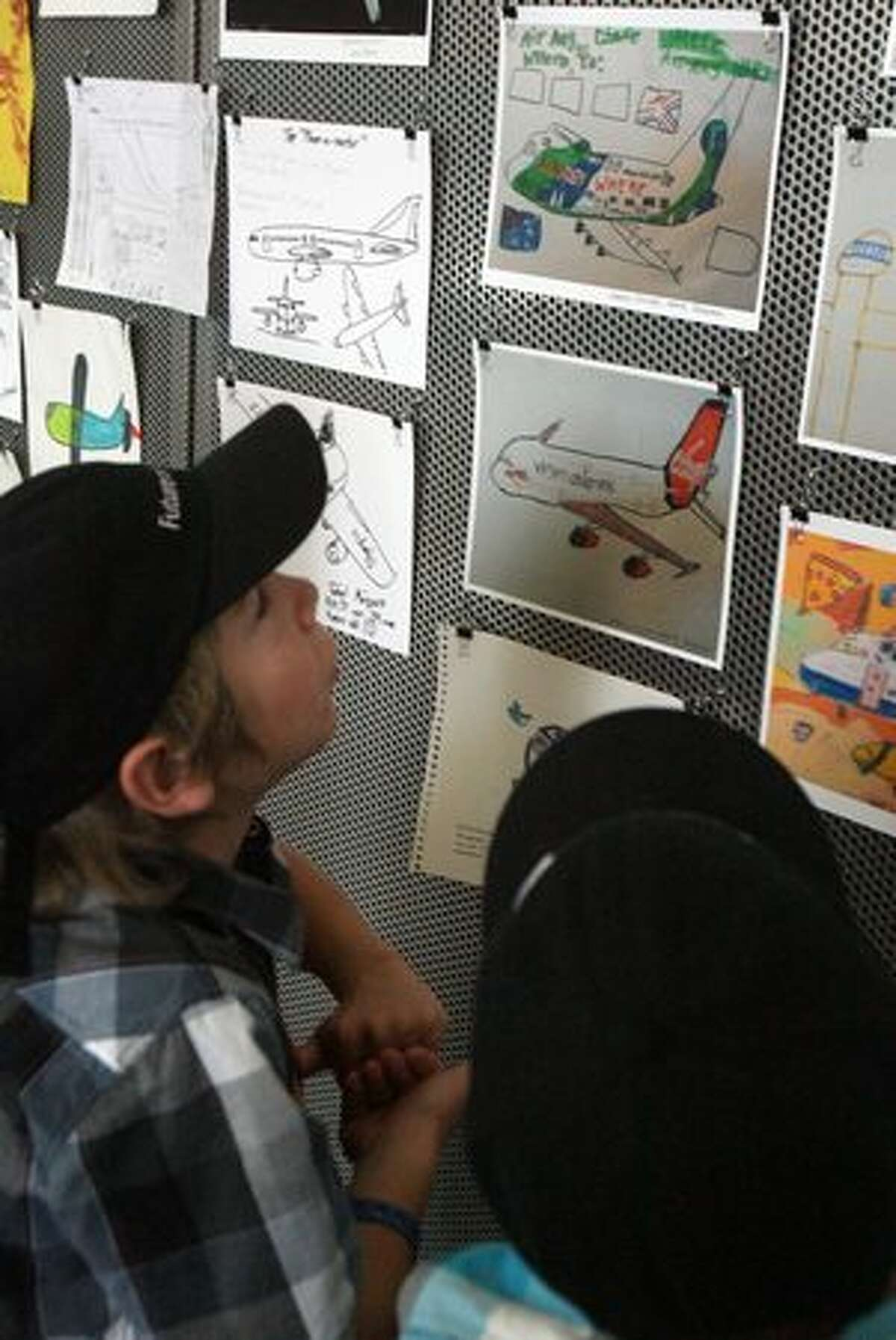 Harry Winsor, 8, looks his entries in an amateur aircraft design drawing show at the Future of Flight Aviation Center, in Mukilteo. The center launched the show in response to a drawing Harry sent to Boeing.