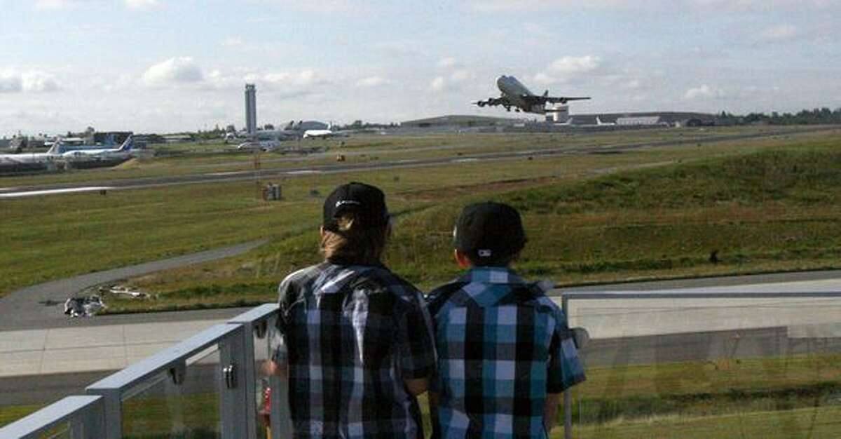 Harry and Charlie Winsor, both 8, stand on the strato deck of the Future of Flight Aviation Center, in Mukilteo, watching a Boeing Dreamlifter take off from Everett's Paine Field. Boeing invited Harry and his family to visit after initially botching a response to a drawing he sent to the company.