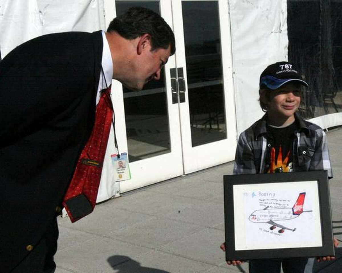 Harry Winsor, 8, presents an airplane drawing to Dave Reese, senior manager of visitor relations for Boeing Commercial Airplanes, on the strato deck of the Future of Flight Aviation Center, in Mukilteo. Boeing invited Harry and his family to visit after initially botching a response to a drawing he sent to the company.