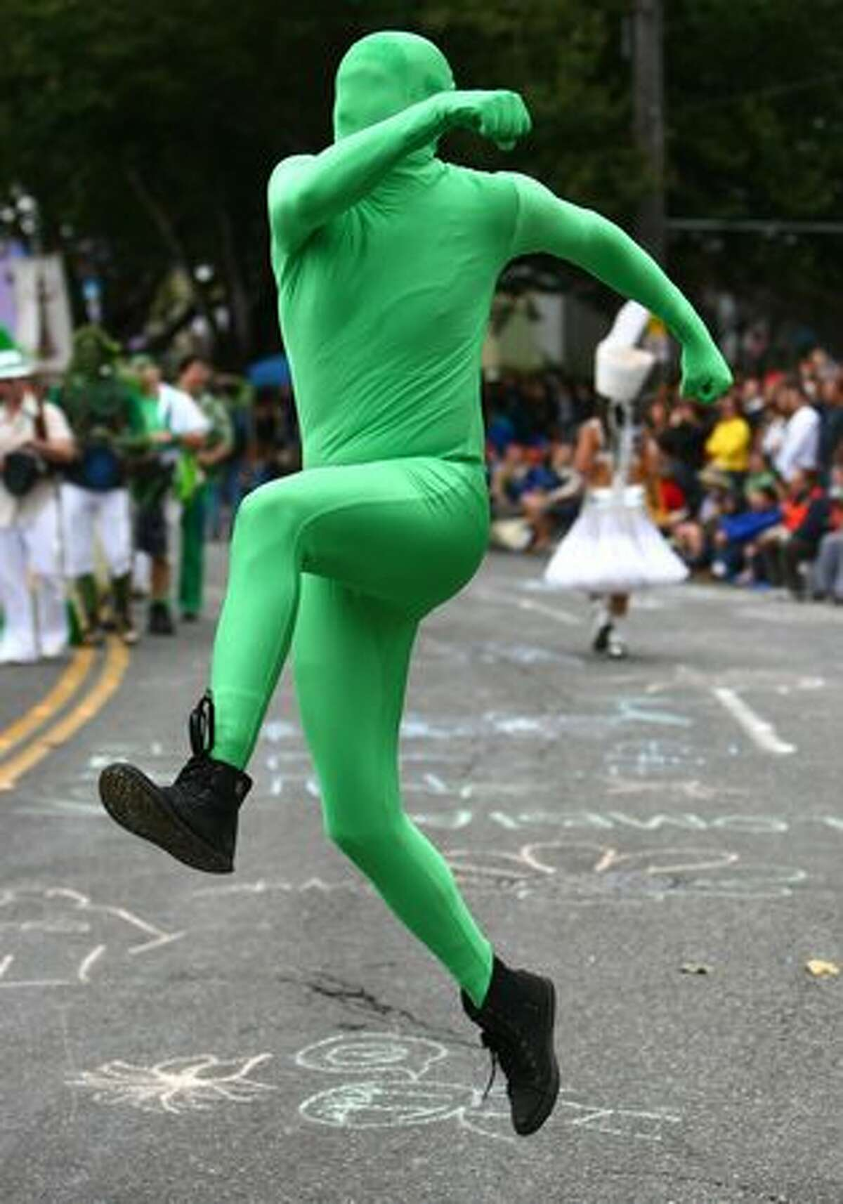A green man runs across North 36th Street during the Fremont Solstice Parade on Saturday June 19, 2010 in Seattle.