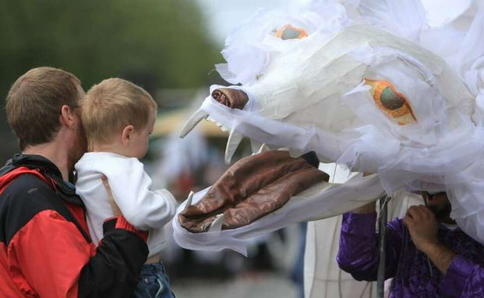 A wolf costume greets a young fan during the Fremont Solstice Parade on Saturday June 19, 2010 in Se