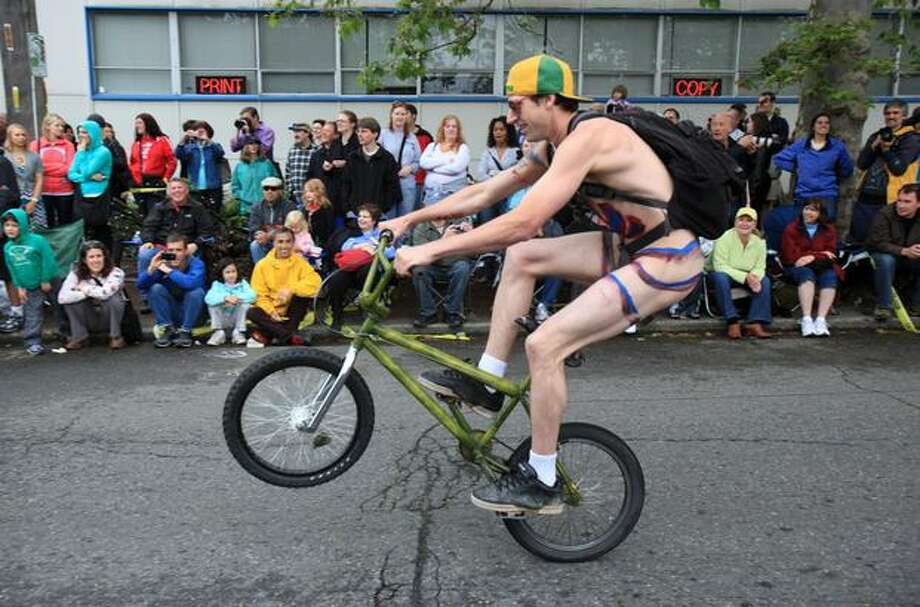 A naked cyclists pops a wheelie during the Fremont Solstice Parade on Saturday June 19, 2010 in Seattle. Photo: Joshua Trujillo, Seattlepi.com