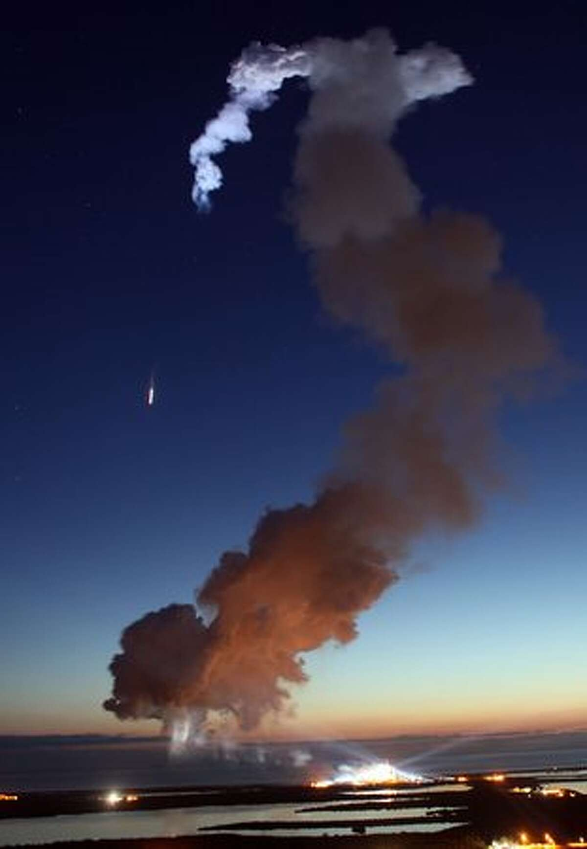 Space shuttle Discovery is seen streaking into space (to the left) as a plume of smoke floats through the air after it blasted off from launch pad 39-A at the Kennedy Space Center on April 5, 2010, in Cape Canaveral, Florida.