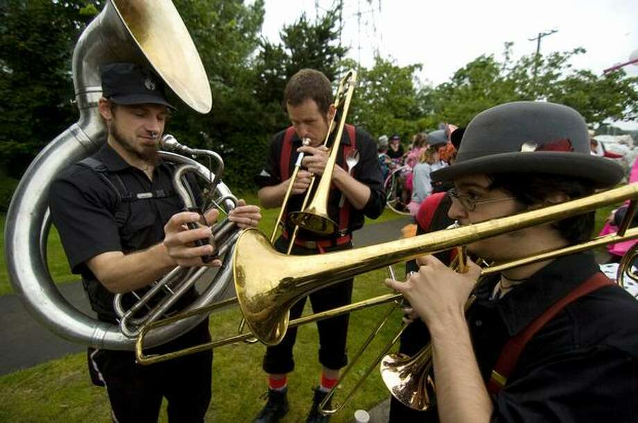 Brass players tune before the Fremont Solstice Parade using a cell phone on Saturday June 19, 2010. Photo: Sang Cho, Seattlepi.com