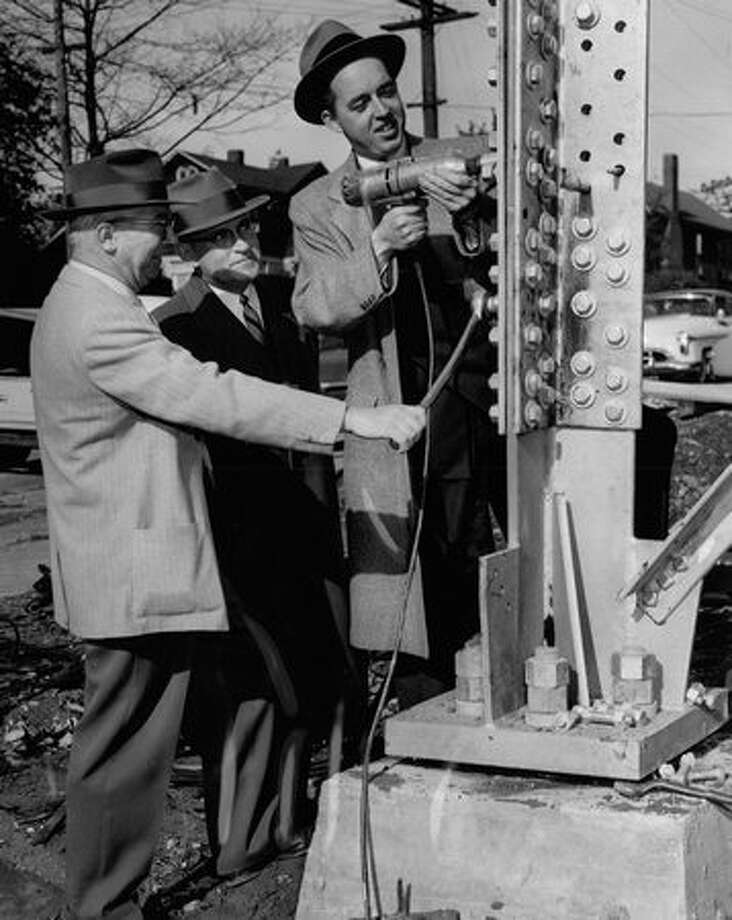 Otto Brendt, general manager of the King Broadcasting Company operates a power wrench on bolts of the KING television tower, November 1953. Photo: P-I File