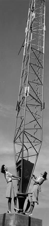 "This photo was taken in June 1941. This was the caption when it ran in the P-I: Dwarfed by one of two soaring 526-foot directional towers, Ella Raines, Warner Brothers' new talent find, and Dori Klemkaski, chosen ""Queen of Queens"" by University of Washington students, explore KIRO's new transmitter, which goes into operation today. Photo: P-I File"