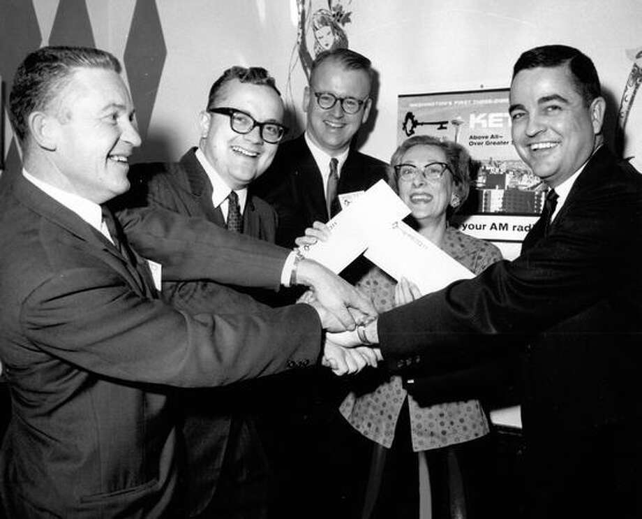 Station personnel of KETO grab hands with winners of a January 1963 contest to determine the exact time and date the new station would go on air. Photo: P-I File