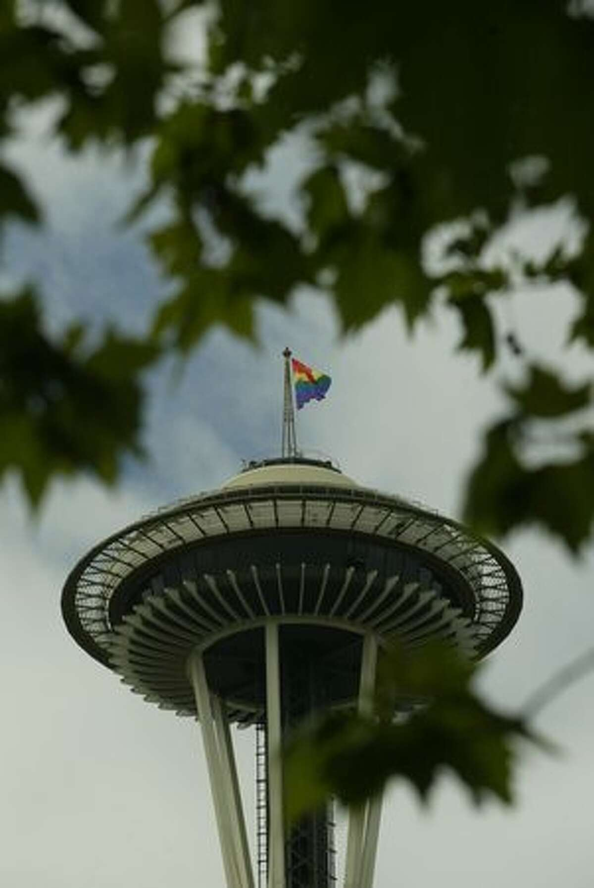 A Gay Pride flag waves from top of Space Needle.