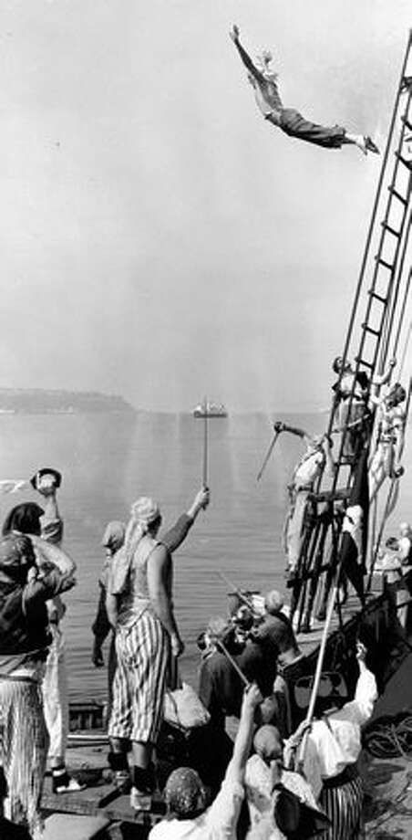 A Seafair pirate dives from the rigging of the three-masted schooner Wawona in Elliott Bay, July 1953. Photo: P-I File
