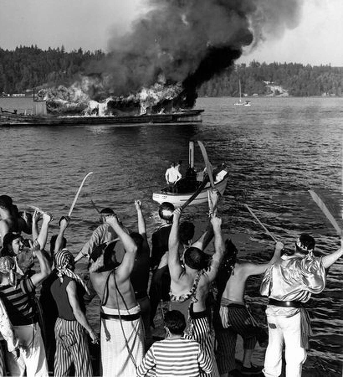 Seafair Pirates burn King Neptune's ship in Andrews Bay off Seward Park tp mark the end of Seafair 1956.