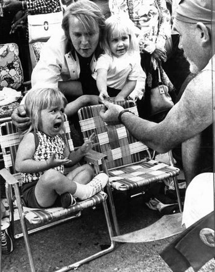 Ted Beck tries to comfort his daughter, Nichole, and held his daughter, Khristina, as a Seafair Pirate greeted them in a 1974 parade. (Grant M. Haller/Seattlepi.com file) Photo: P-I File