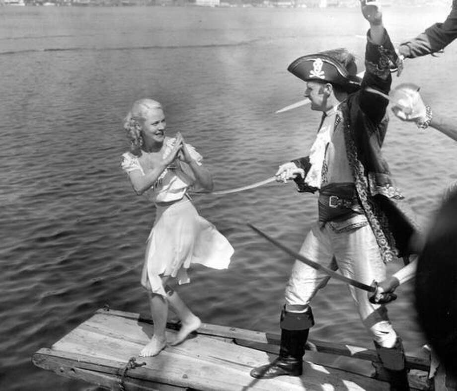 Betty Skally walks the plank after Davy Jones and his pirates captured the schooner Fantome in Lake Union. In this 1951 photo, she pleads with Captain Kidd, Bob McCurdy. Photo: P-I File