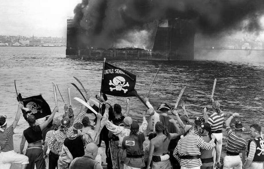 Seafair Pirates watch as King Neptune IX's drydock burns, August 1958. Photo: P-I File