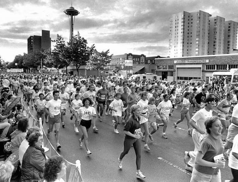 Runners go past spectators on Fourth Avenue and Battery Street during the 1987 Torchlight Run.