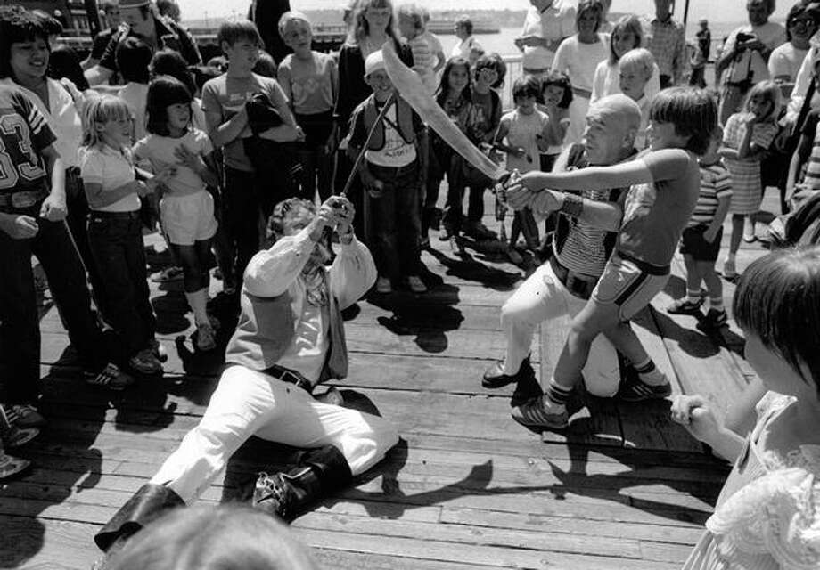 Bob Dorsey, left, falls to the ground after losing a battle against Bob Smyth and 9-year-old Eric Schuler during the invasion of the Seafair Pirates at Waterfront Park, July 19, 1984. (Mike Bainter/Seattlepi.com file) Photo: P-I File