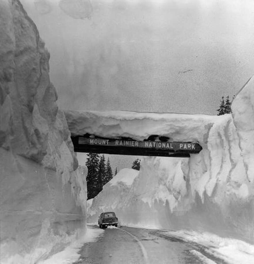 This snow-shrouded arch and the high walls of snow on the Chinook Pass Highway mark the summit of the pass and the east entrance to Mount Rainier National Park in 1956. (Hack Miller/P-I) Photo: P-I File