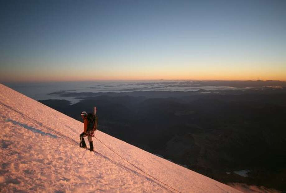 Rainier Mountaineering, Inc. (RMI) climbing guide Stuart Robertson rest-steps his way up Mt. Rainier's east face soon after sunrise on Wednesday, August 23, 2006. A typical summit trip led by RMI leaves Camp Muir at about 1 a.m. and reaches the top around 8 a.m. (MIKE KANE/P-I) Photo: P-I File