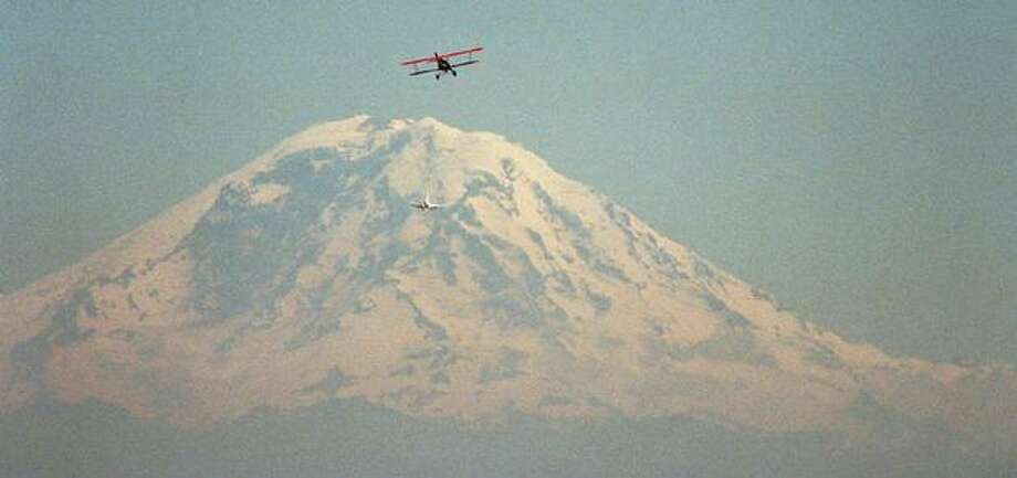 Galvin Flying Service biplane returns to Boeing field for a landing with a spectacular view of Mount Rainier behind it. Photo: P-I File