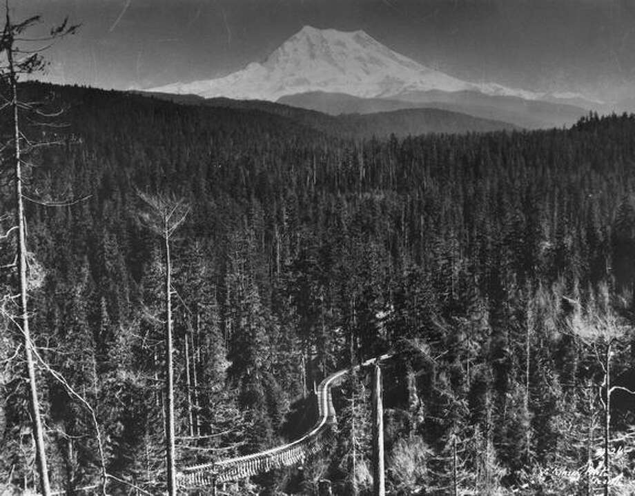 Circa 1924 - Mount Rainier stands boldly above thousands of acres of virgin timber, long since vanished. In foreground is a flume which carried water to Electron plant of Puget Sound Power and Light Co. from headwaters of Puyallup River. Photo: P-I File