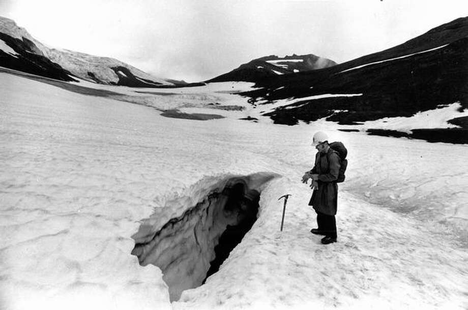 Dale Thompson, chief naturalist of Mt. Rainier National Park, looking down at entrance to Paradise ice caves in September 1978. (Grant Haller) Photo: P-I File
