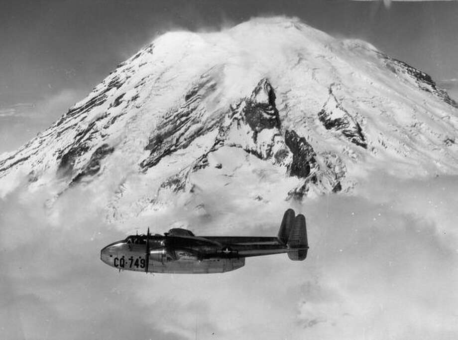 1947 - C-82 transport of 12th Air Force, McChord Field, loaded with 42 fully equipped infantry men of Second Infantry Division, passes Mount Rainier on a practice flight before leaving for winter maneuvers in Alaska's Big Delta area. (Photo by U.S. Army Air Forces). Photo: P-I File