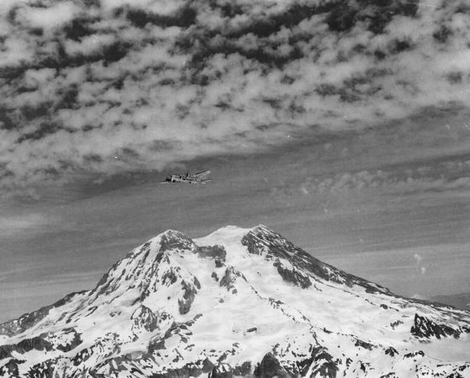 A coast guard plane in flight over majestic Mount Rainier, July 1949. (Photo by United States Coast Guard). Photo: P-I File
