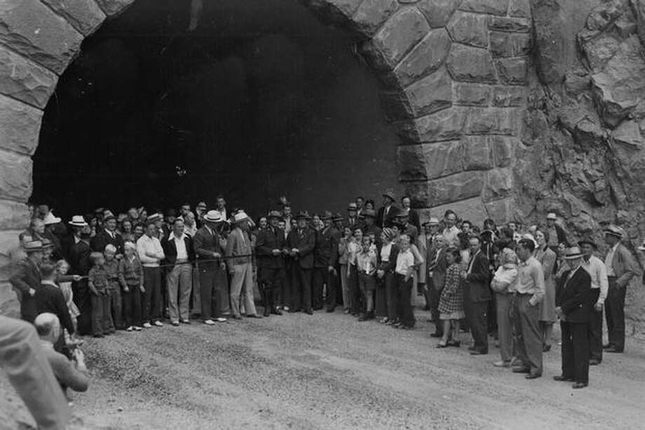 A ribbon across the south portal of a 500-foot tunnel was cut to open the East Side road on Mount Rainier in June 1940, while crowds of visitors looked on. Holding the scissors is O.A. Tomlinson, then park superintendent, while Fred Norman of Raymond, president of the Southwest Washinton Good Roads Association, holds the Ribbon. Photo: P-I File