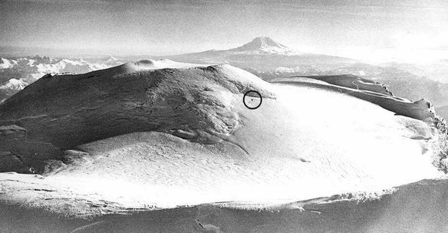 January 1979: A plane (inside circle) sits 300 feet below the summit of Mount Rainier after a crash landing. Mount Adams looms in the background. (Grant Haller/P-I) Photo: P-I File
