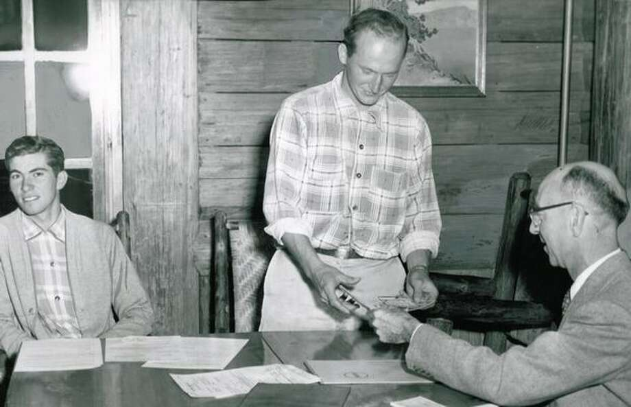 September 1956: The Rev. Earle Johnson hands money to U.S. Commissioner Earl Clifford at Longmire after he and Don Richardson (left) were fined $25 each for an unauthorized attempt to climb Mount Rainier, which brought rescue parties to their aid. (John 'Hack' Miller/P-I) Photo: P-I File
