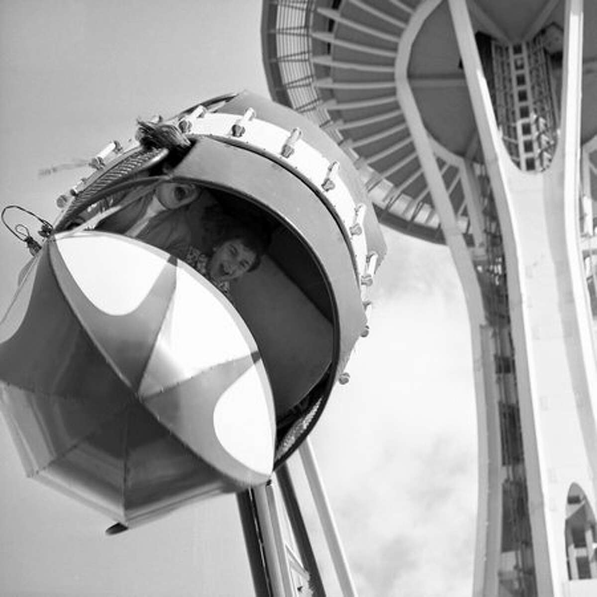 The Seattle Center's Fun Forest, which was initially formed as the Gayway entertainment area for the 1962 World's Fair, added major rides in 1964 to what had been primarily an assortment of carnival games. In this spring 1965 photo, Mary Anne Norton, age 13, and Kristy Davis, 12, enjoy the Rolo Plane. (Seattlepi.com file/MOHAI collection)