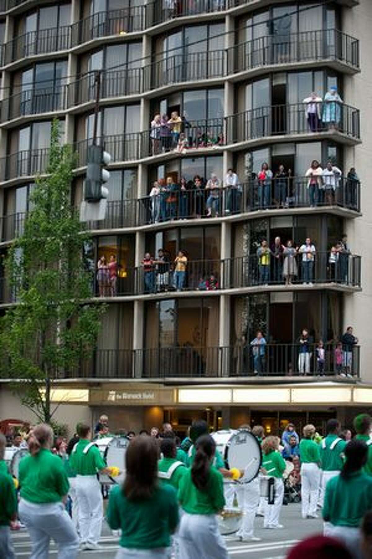 Spectators watch from the balconies of the Warwick Hotel as the parade passes below.