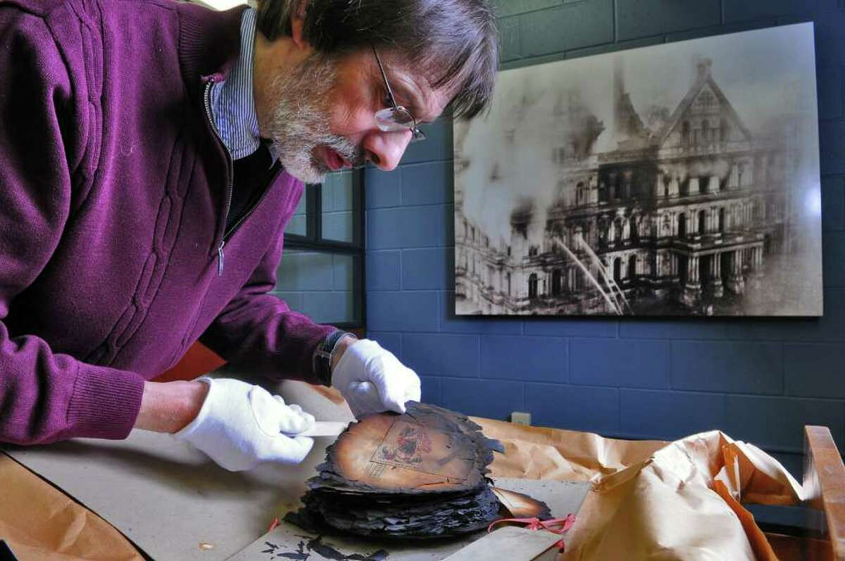 New York State Library Senior Librarian Paul Mercer carefully looks at the remains of papers salvaged from the Capitol fire of March 29, 1911, that had been in storage in the library on Thursday March 10, 2011 in Albany, NY. A photograph of the fire is on the wall in the background. ( Philip Kamrass / Times Union )