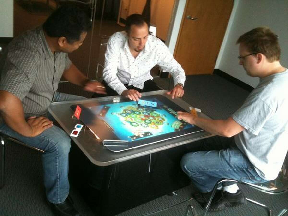 """Microsoft PR rep Eric Havir, center, tries out """"The Settlers of Catan"""" for Microsoft Surface with game developers Joe Engalan, left, and Filip Skakum from Vectorform."""