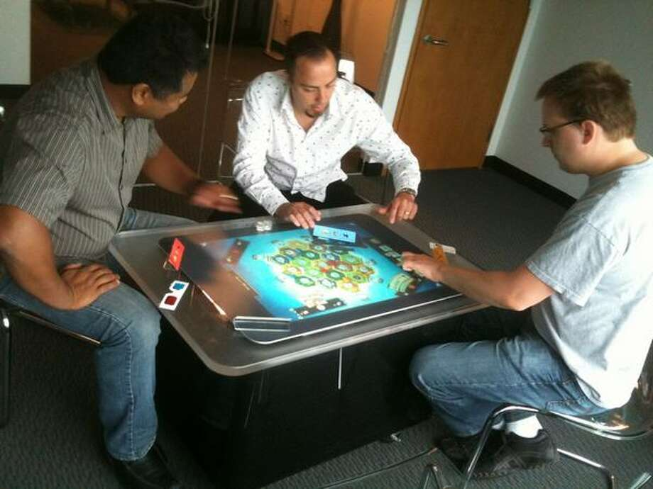 "Microsoft PR rep Eric Havir, center, tries out ""The Settlers of Catan"" for Microsoft Surface with game developers Joe Engalan, left, and Filip Skakum from Vectorform. Photo: Nick Eaton, Seattlepi.com"