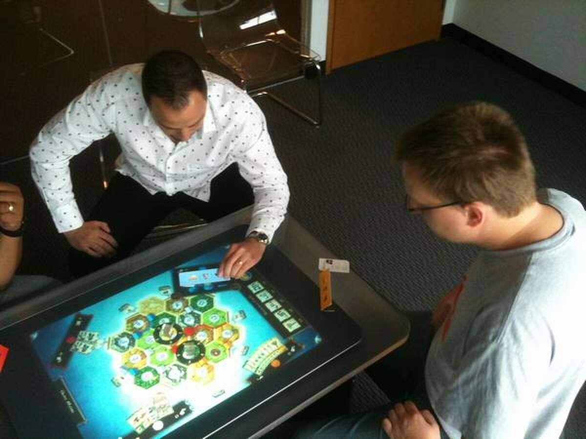 "Microsot's Eric Havir uses a visor to peek at his virtual ""Settlers of Catan"" playing cards as he plays against Vectorform game developer Filip Skakum."