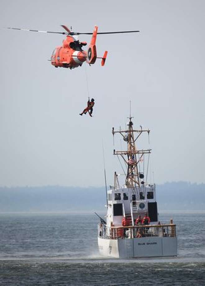 A U.S. Coast Guardsmen performs an exercise during U.S. Navy Fleet Week's Parade of Ships in Elliott Bay along the Seattle waterfront on Wednesday August 4, 2010. The parade is part of Seattle's annual Seafair celebration. Photo: Joshua Trujillo, Seattlepi.com