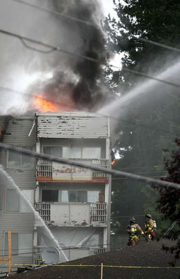 Flames flare up in the northwest corner of the complex. Photo: Clifford DesPeaux, Seattlepi.com