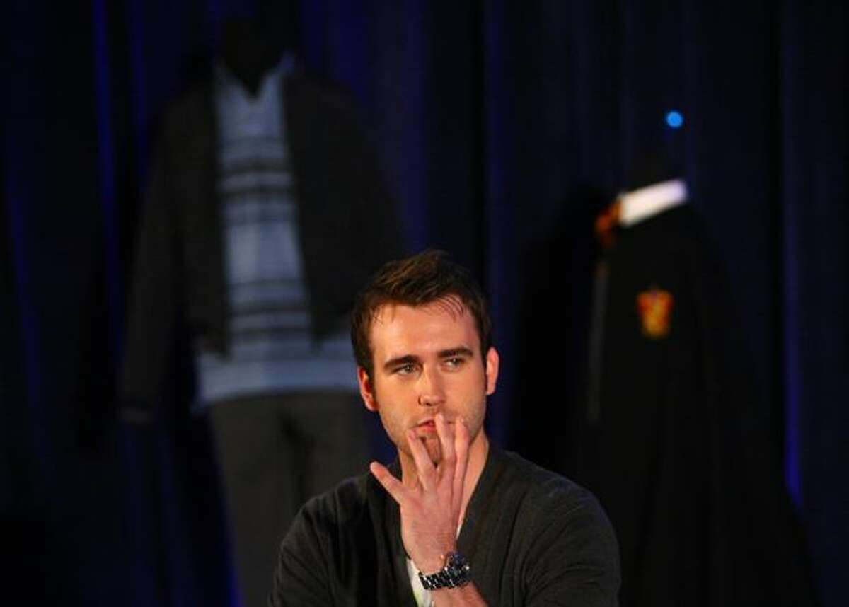 Actor Matthew Lewis, who plays the character Neville Longbottom in the Harry Potter films, speaks onstage at the Pacific Science Center. Behind Lewis are two of his costumes from the film.
