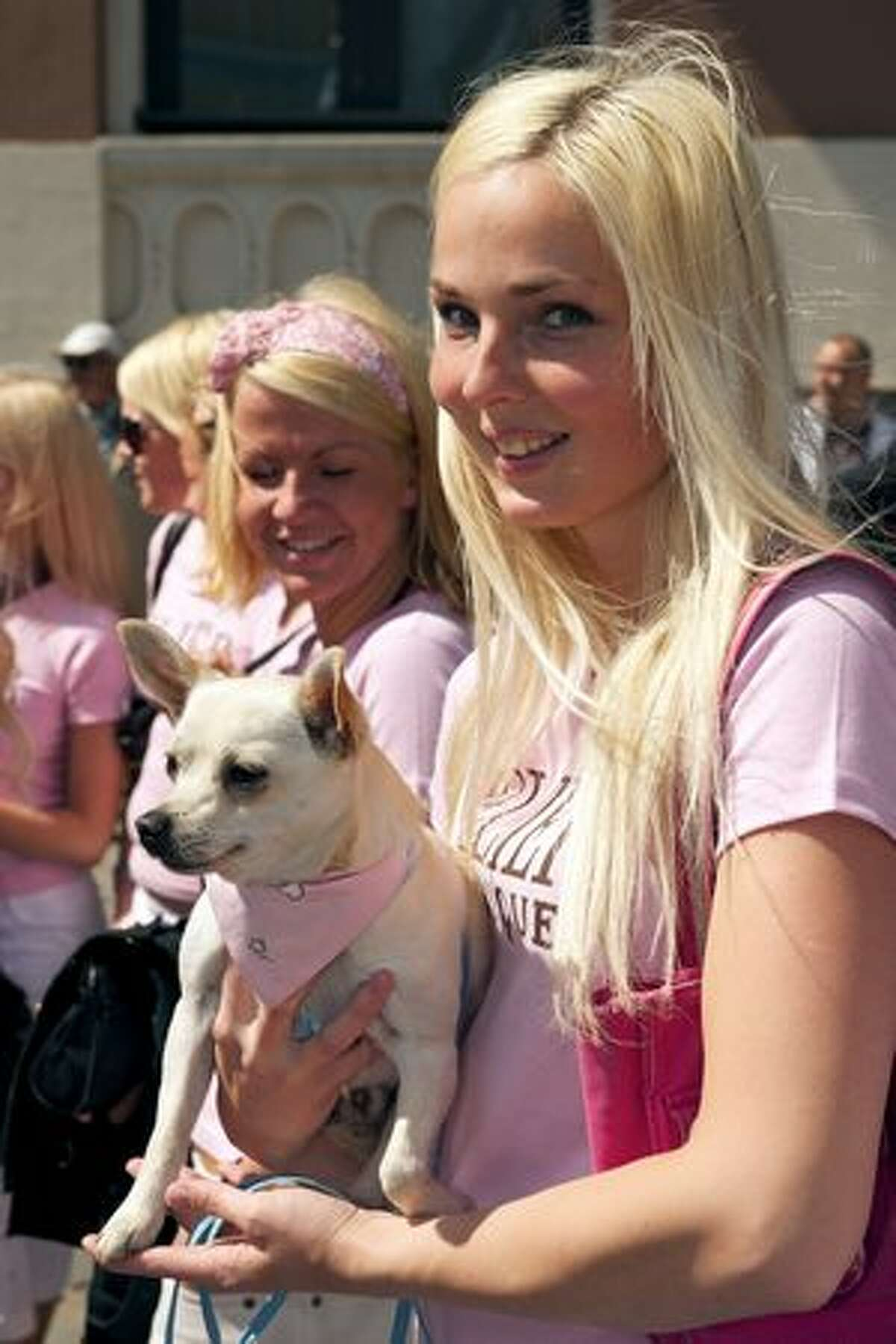 A Blond woman poses with her dog as they parade through the streets of Latvia's capital Riga during a Blond weekend.